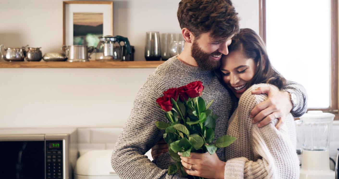 Man and woman smiling and embracing, with red roses in woman's hand.