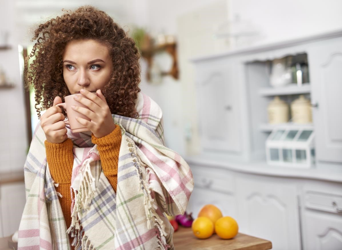 Woman drinking out of mug, wrapped in scarf.