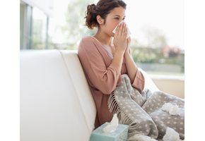 Woman sitting on the couch, blowing her nose into a tissue.